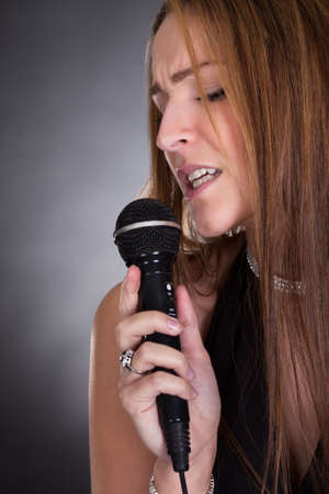 Portrait Of Young Beautiful Woman Singing In Microphone photo