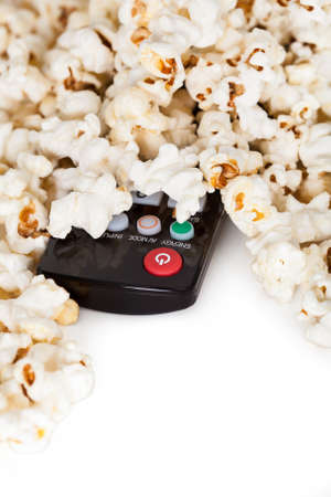 Close-up Of Remote Control And Popcorn Over White Background photo