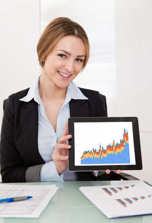 Happy Young Businesswoman Presenting Charts On Digital Tablet photo