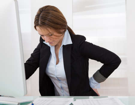 woman pain: Business Woman With Back Pain Holding Her Aching Hip Stock Photo