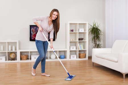 servicio domestico: Retrato de la mujer joven trapear el piso en casa Foto de archivo