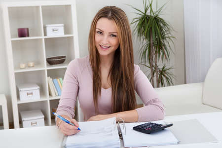 tax consultants: Young Worried Woman Calculating Bills At Home Stock Photo