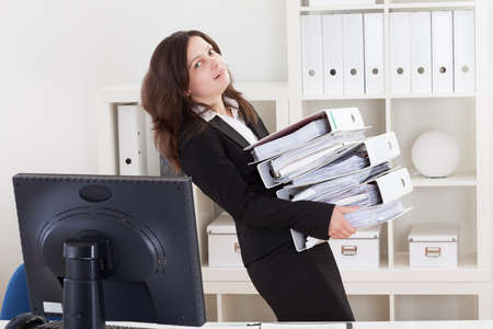 Businesswoman Carrying Stack Of Folders In Office photo