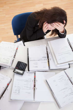accountant: Stressed Businesswoman Working In Office With Stack Of Folders