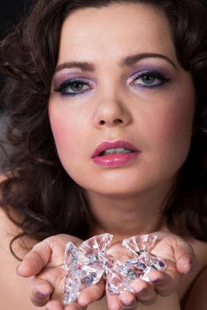 Portrait Of Young Beautiful Woman Holding Diamonds photo
