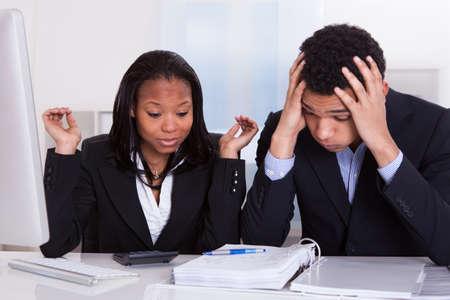 persona confundida: Preocupado hombre y de la mujer en el escritorio en la oficina