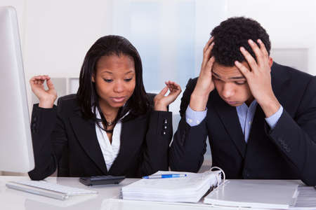 taxes budgeting: Worried Business Man And Woman At Desk In Office