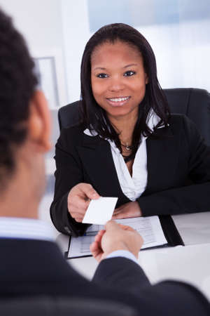 Businesswoman Offering Visiting Card To Man In Office photo