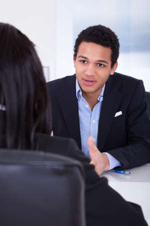 conversations: Portrait Of Businessman Discussing With His Co-worker In Office Stock Photo