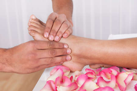 foot model: Close-up Of Hand Massaging Foot In Spa