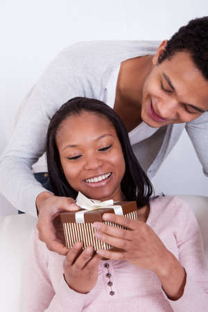 Portrait Of Young Man Surprising Woman With Gift Box photo