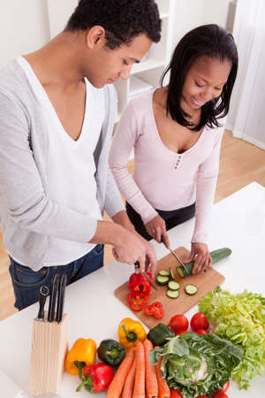 vegetables young couple: Portrait Of Couple Chopping Vegetables In Kitchen Stock Photo