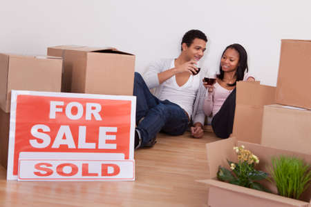 moving in: Portrait Couple Sitting Among Moving Boxes Making Celebration In House