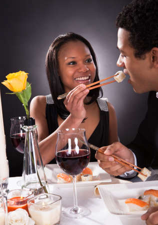 dinner couple: Portrait Of Female Feeding Sushi To Male At Dinner Stock Photo