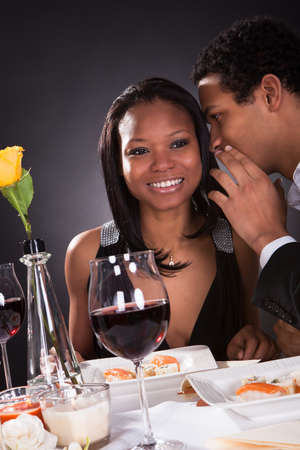 Portrait Of Man Whispering To Girlfriends Ear At Dinner photo