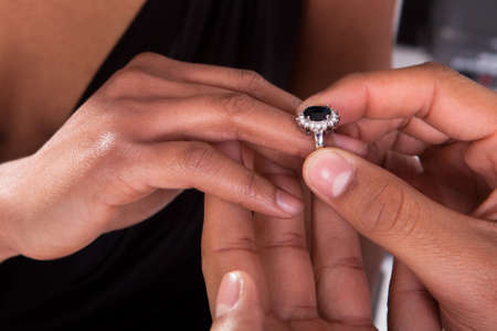 engagement: Close Up Of Male Hand Inserting An Engagement Ring Into A Finger Stock Photo