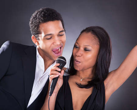 Portrait Of African Couple Singing With Microphone Over Grey Background photo