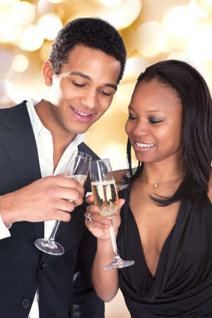 Portrait Of African Couple Enjoying Champagne Drink Over Grey Background photo