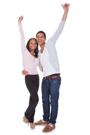 young cheering: Happy Couple Raising Hand Over White Background