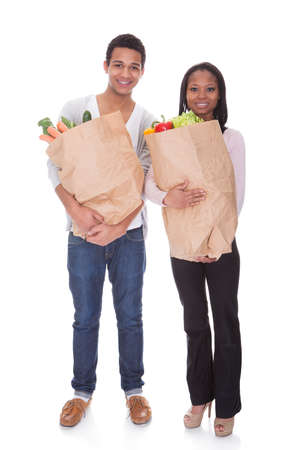 Couple With A Grocery Bag Isolated Over White Background photo