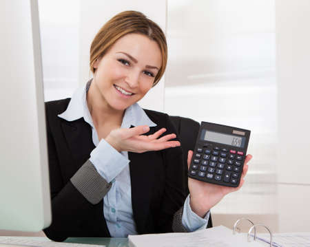 Portrait Of Happy Young Businesswoman Showing Calculator photo