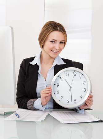 Portrait Of Young Businesswoman Holding Clock In The Office photo