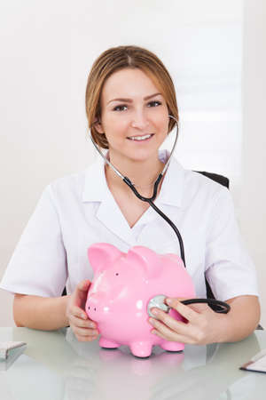 Portrait Of Young Female Doctor Examining Piggybank photo