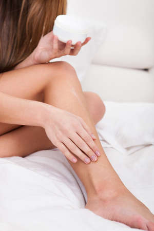 foot cream: Close-up Of A Woman Applying Lotion On Her Feet Stock Photo