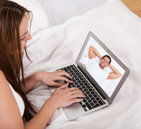 Portrait Of Young Woman Video Chatting With A Man photo