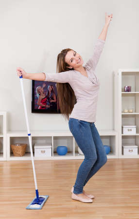 Portrait Of Young Woman Dancing In Home While Cleaning Floor photo