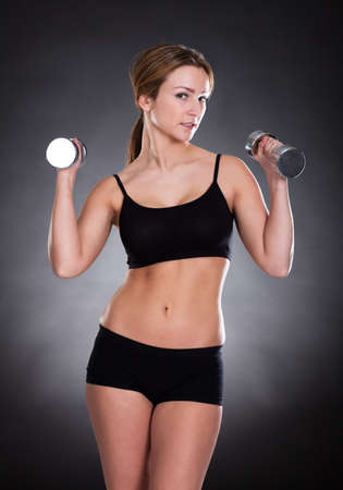 Portrait Of Young Woman Exercising With  Dumbbells photo