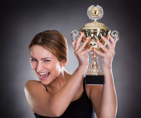 sportsperson: A Young Female Player Raising Her Trophy Stock Photo