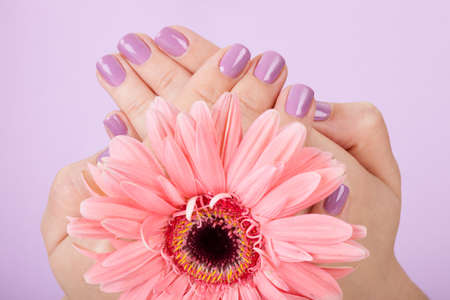 Human Fingers With Beautiful Manicure Isolated Over Purple Background photo
