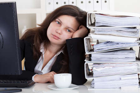 Stressed Businesswoman Working In Office With Stack Of Folders photo