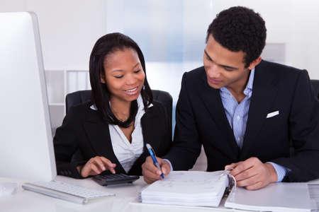 contabilidad financiera cuentas: Dos personas de negocios C�lculo Finanzas Juntos En La Oficina