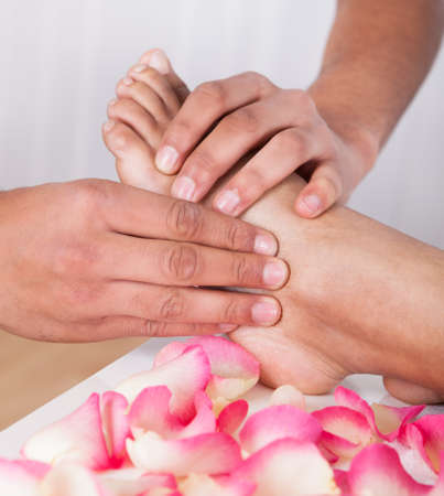 girl feet: Close-up Of Hand Massaging Foot In Spa