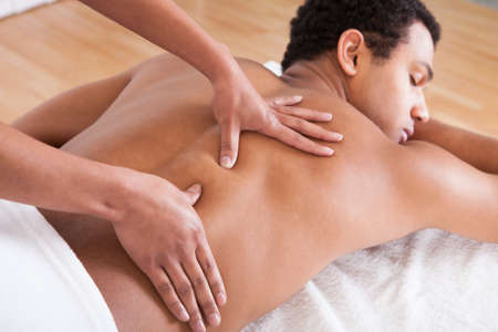 male massage: Portrait Of Man Receiving Massage Treatment From Female Hand Stock Photo