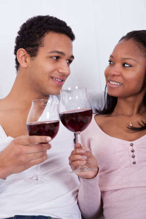 proposing a toast: Portrait Of Young African Couple Toasting Red Wine