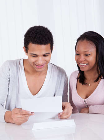 good news: Portrait Of Happy Young Couple Looking At Paper