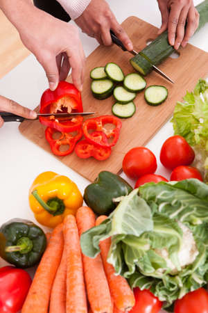 sharing food: Portrait Of Couple Chopping Vegetables In Kitchen Stock Photo