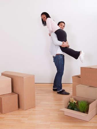 Portrait Of Man Carrying Woman On Shoulder In House photo
