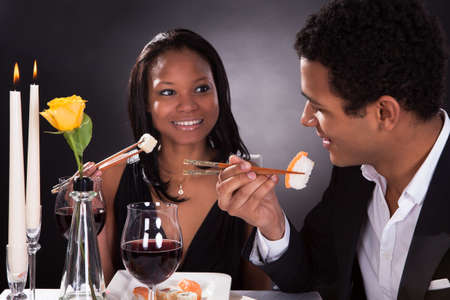 Portrait Of Romantic Couple Eating Sushi At Dinner Stock Photo