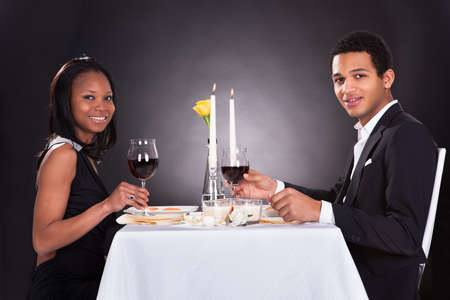 Portrait Of Romantic Couple Toasting Red Wine At Dinner photo