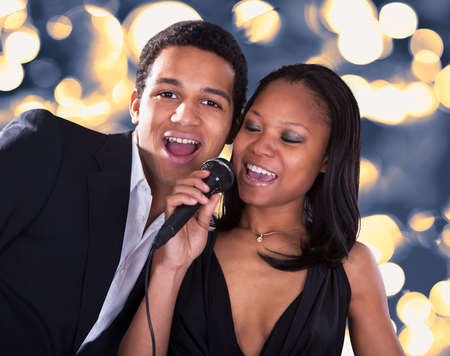 to sing: Portrait Of African Couple Singing With Microphone Over Grey Background Stock Photo
