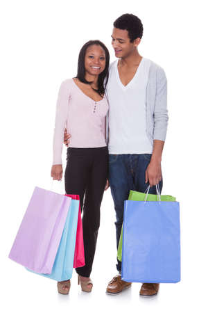 holiday spending: Portrait Of Young Couple With Shopping Bags Over White Background Stock Photo
