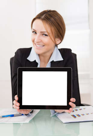 Happy Young Businesswoman Presenting Digital Tablet In The Office photo