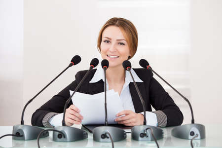 press conference: Young Cheerful Businesswoman Giving Speech In Conference