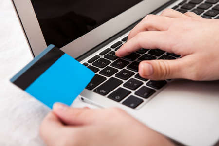 Close-up Of Hand Using Credit Card And Laptop For Online Shopping Stock Photo - 19382944