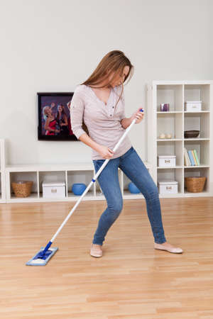 domestic chore: Portrait Of Young Woman Dancing In Home While Cleaning Floor