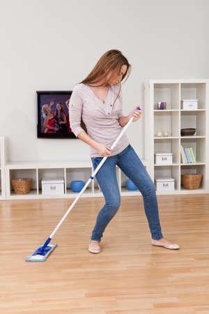 empleadas domesticas: Retrato de joven mujer bailando en casa mientras Floor Cleaning Foto de archivo